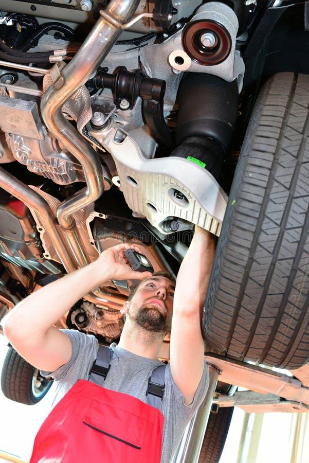 Auto mechanik naprawia pojazd w warsztacie obraz royalty free