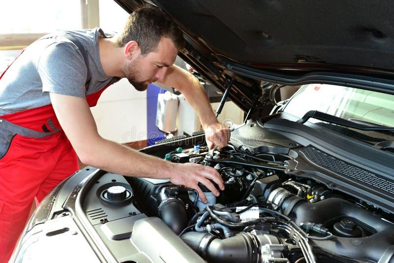Auto mechanik naprawia pojazd w warsztacie fotografia royalty free