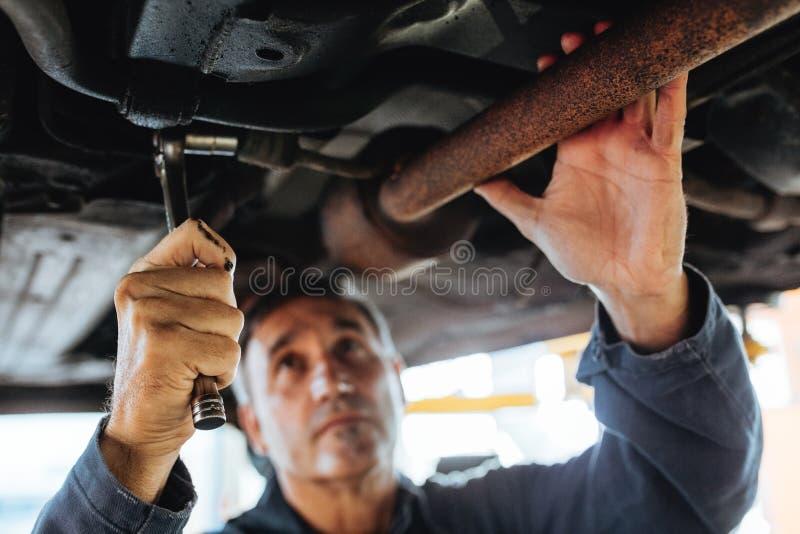 Auto mechanik naprawia samochód w staci obsługi zdjęcie royalty free