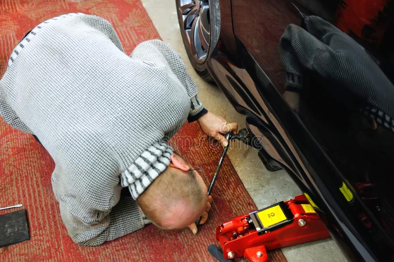 Auto mechanik patrzeje pod samochodem instalować dźwigarki zdjęcia royalty free