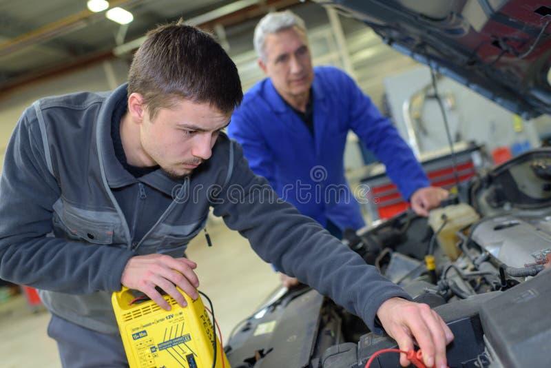 Auto mechanik pokazuje praktykanta utrzymania silnika obraz stock