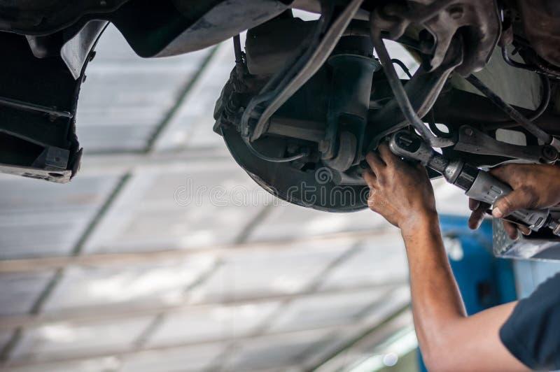 Auto mechanika azjatykci sprawdza rygiel pod dwoistym wishbone zawieszeniem ręką z narzędzia samochodowym dźwignięciem fotografia stock