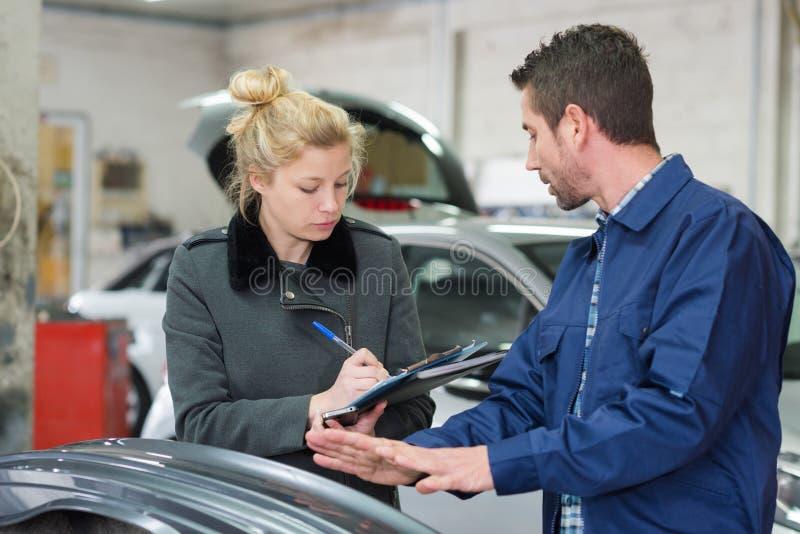 Auto mechanika i kobiety klient w gara?u obraz royalty free