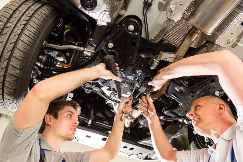 Auto mekaniker som arbetar under bilen arkivbilder