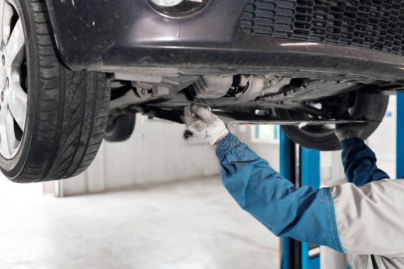 Auto mekaniker som arbetar under bilen på en elevator Olje- ändring royaltyfri bild