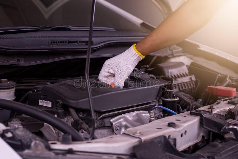 Auto mekaniker som kontrollerar motorn för olje- nivå, automatisk underhållsbilreparation arkivbild