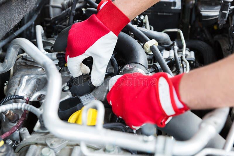 Auto mekaniker som kontrollerar trådar för tändstift för bilmotor royaltyfri fotografi