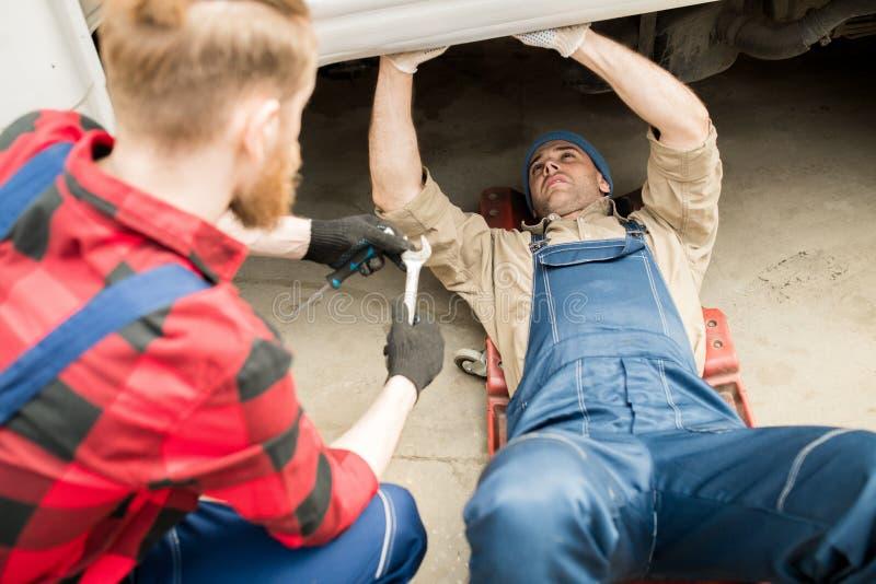 Auto mekaniker Under Truck fotografering för bildbyråer