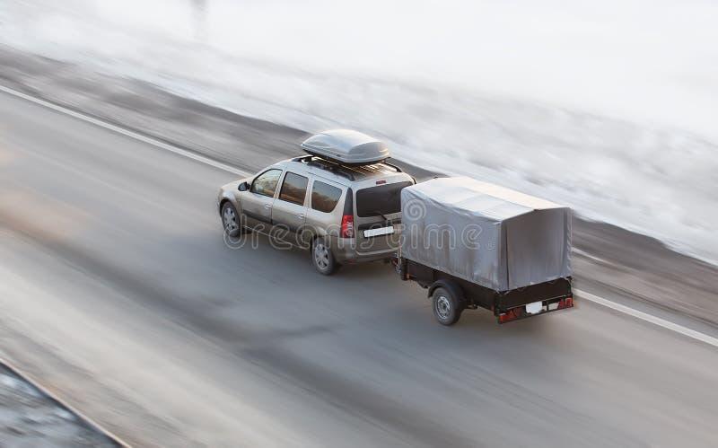 Auto met aanhangwagenritten op de de winterweg royalty-vrije stock afbeeldingen