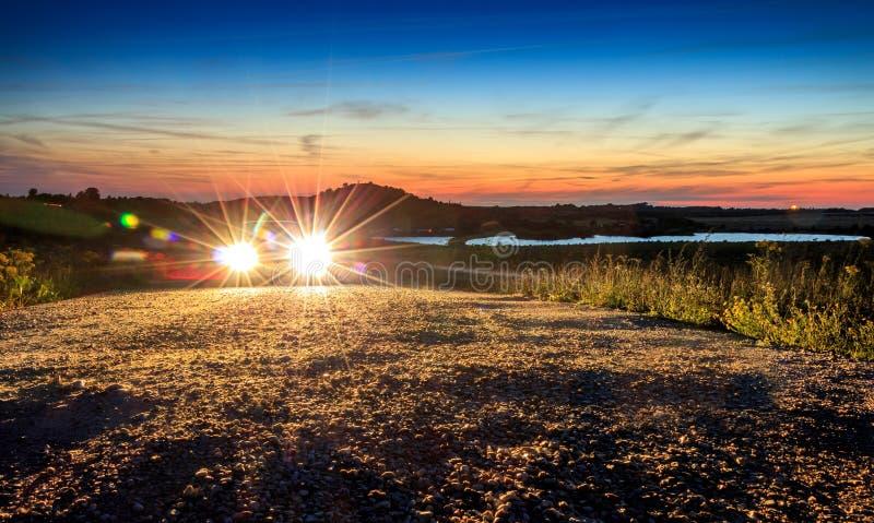 Auto met helder licht in mooie de zonsondergangzon van het berglandschap royalty-vrije stock afbeelding