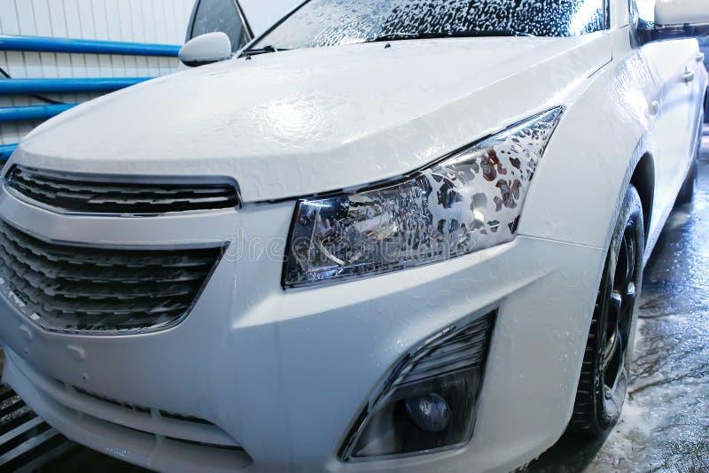 Auto met schuim in autowasserette wordt behandeld die royalty-vrije stock afbeeldingen