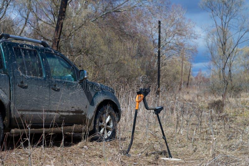 Auto, Metalldetektor und Schaufel nicht für den Straßenverkehr auf dem Gebiet stockbild