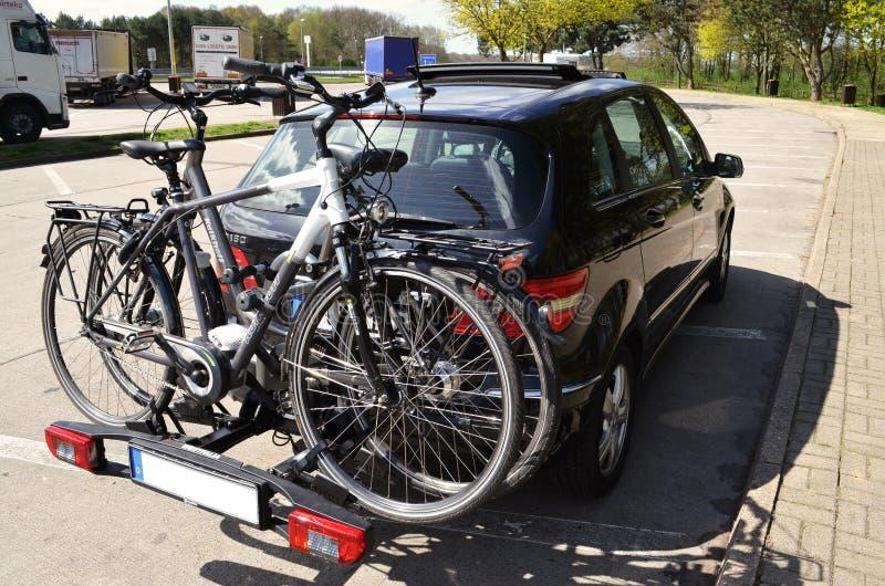 Auto mit einer Zyklusfördermaschine und zwei Fahrrädern auf einem Landstraßenpicknickplatz lizenzfreie stockfotos
