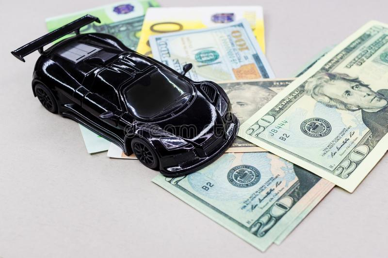 Auto money, background and texture for finance. Miniature car model and Financial statement with coins. Finance and car loan, saving money for a car or material stock image