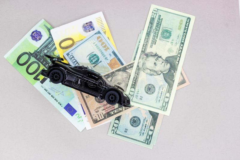 Auto money, background and texture for finance. Miniature car model and Financial statement with coins. Finance and car loan, saving money for a car or material stock photography