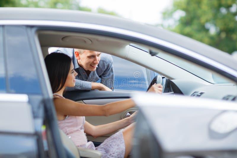 Auto negócio, venda do carro, consumição e conceito dos povos - carro de compra dos pares felizes na feira automóvel ou no salão  imagem de stock
