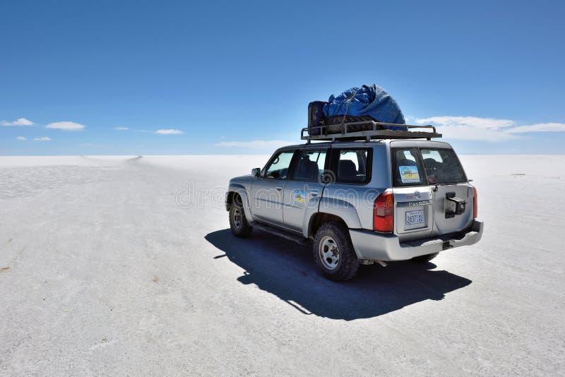 Auto nicht für den Straßenverkehr auf Oberfläche von See Salar de Uyuni lizenzfreie stockbilder