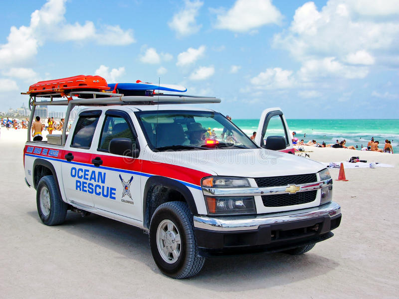 Auto ocean rescue. Miami, Florida, USA - May 28, 2007: A woman in a jeep equipped for rescue at sea, stands still parked at the edge of the beach, ready to royalty free stock image