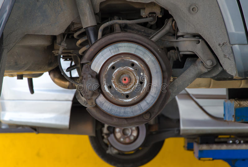 Auto onder reparatie op hijstoestel bij benzinestation stock foto