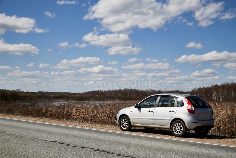 Auto op asfaltweg in de vroege lente dichtbij bos en blauwe hemel met wolken Landschap binnen in aardige de lentedag Rusland stock foto