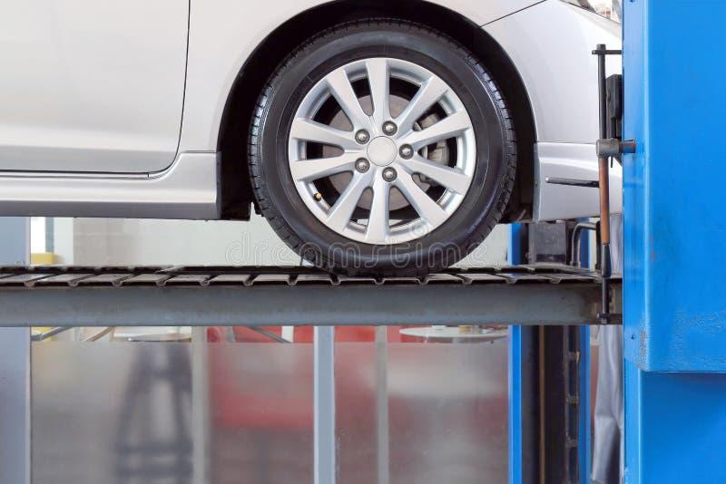 Auto op de dienstgarage met mechanische hulpmiddelen voor auto onder reparatie, autowerktuigkundige die in het centrum van de aut royalty-vrije stock foto's