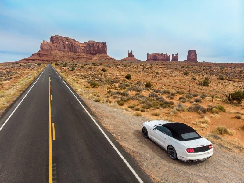 Auto op de weg van het woestijnasfalt in Monumentenvallei wordt geparkeerd in Arizona dat Van de de Westkustreis van de V.S. de b royalty-vrije stock foto