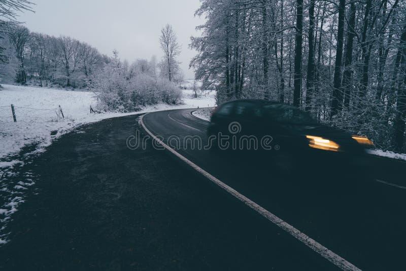 Auto op de winterweg door bos stock afbeeldingen