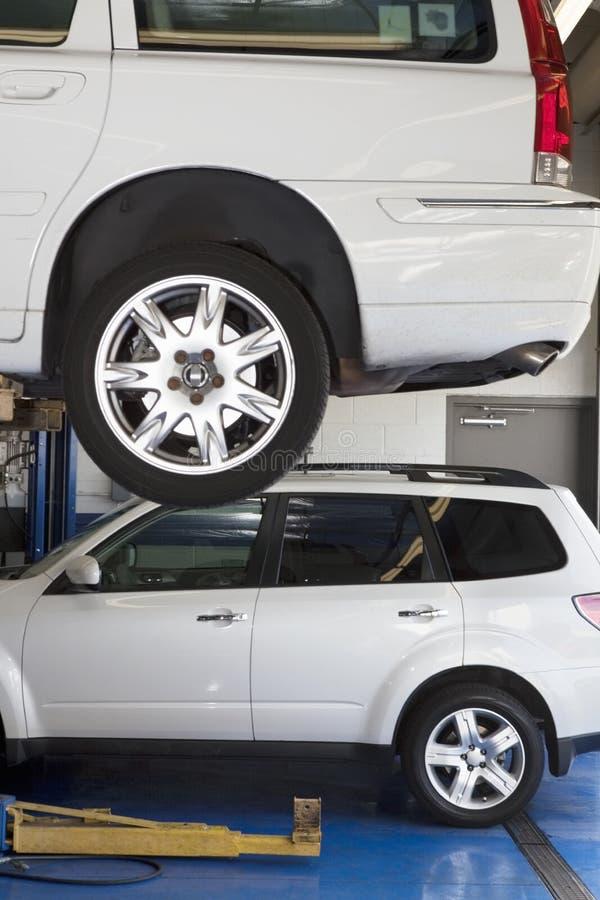 Auto op hijstoestel in automobiele reparatiewerkplaats stock foto