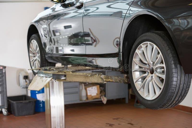 Auto op hijstoestel bij reparatiewerkplaats stock afbeeldingen