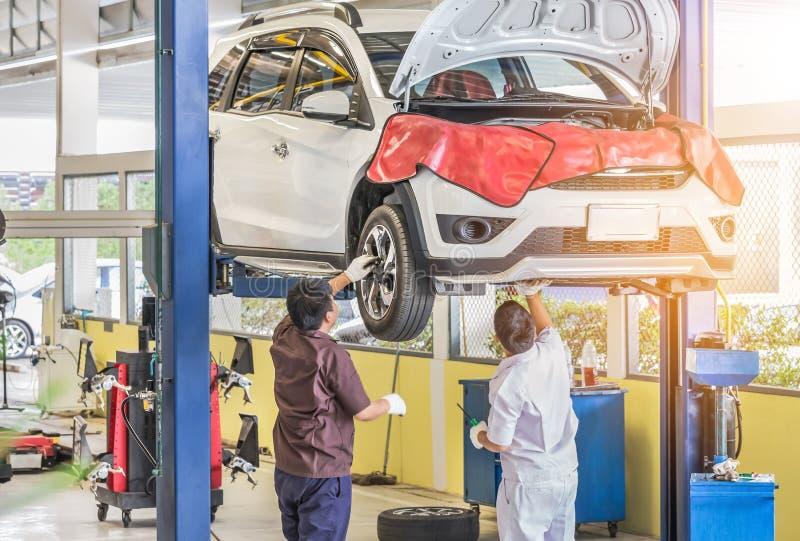 Auto op lift aan reparatieopschorting in de garage met het mechanische werken onderaan opgeheven auto aan de hub van het verander stock afbeeldingen