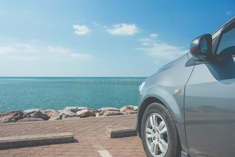 Auto op parkeerterrein bij kust dichtbij het strand met zeegezicht wordt geparkeerd en blauwe hemel op de achtergrond die stock fotografie