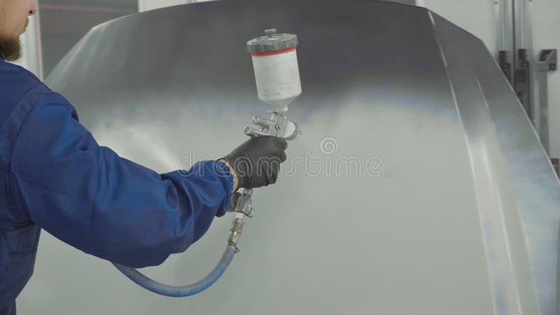 Auto painter spraying white paint on car hood in special booth. Auto painter spraying white paint on car spare bonnet in special booth. Painting vehicle parts at royalty free stock image