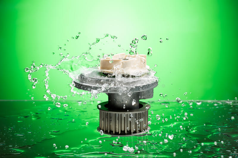 Auto parts, engine cooling pump in water splash on green background royalty free stock photos