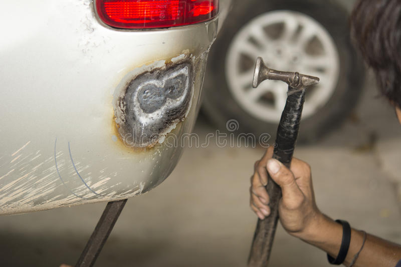 Auto repair man worker flatten and align metal body car with ham. Mer in automotive industry stock image