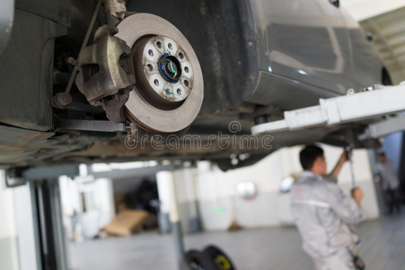 Auto repair service. Car on the jack, Changing tire and checking the chassis stock image