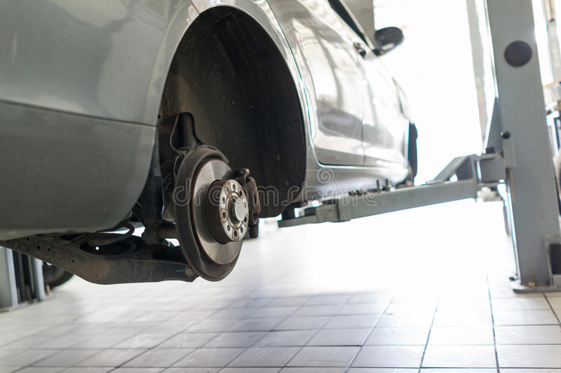 Auto repair service. Car on the jack,Changing tire and checking the chassis royalty free stock photo