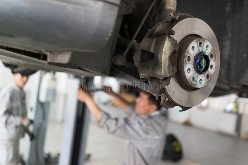 Auto repair service. Car on the jack,Changing tire and checking the chassis royalty free stock image