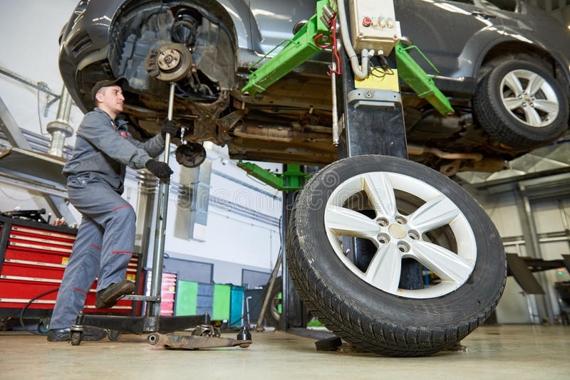 Auto repair service. Mechanic works with car. Suspension at garage shop royalty free stock image