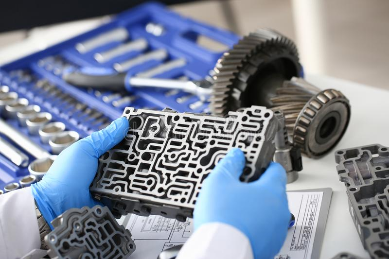 The auto repair service repairman in automatic gearboxes. Holds in his hand in blue protective gloves the hydroblock detail dehydrates the diagnostics and royalty free stock photos
