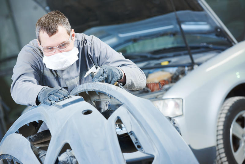 Auto repairman grinding autobody bonnet. Auto body repairs. Repairman mechanic worker grinding automobile car bonnet by sand paper in garage workshop royalty free stock photography