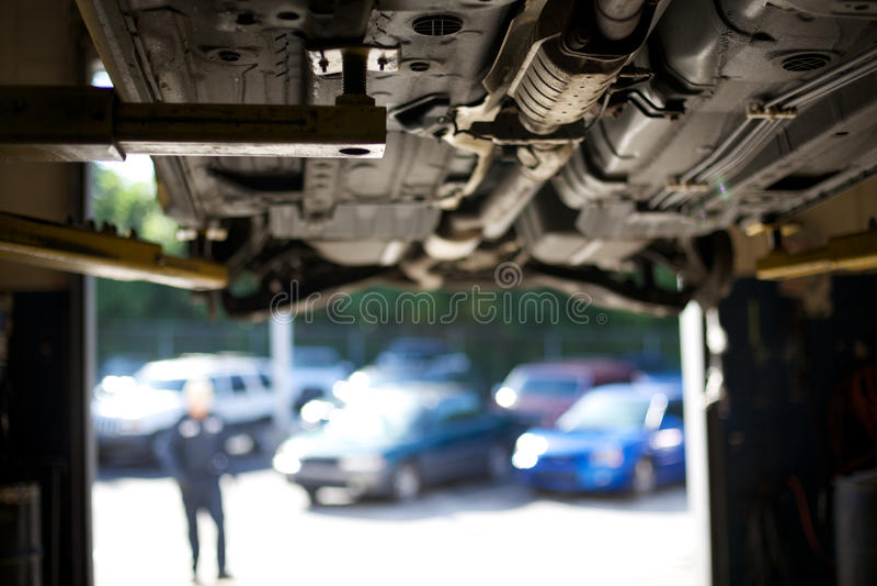 Auto reparatiewerkplaats, arbeider stock afbeelding