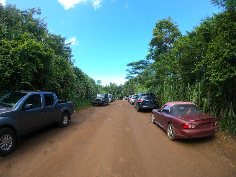 Auto's bij trailhead aan Geheim Strand Kauai Hawaï worden geparkeerd dat stock fotografie