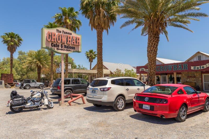 Auto's en motorfiets op de parkeerauto voor Crowbar Cafe en Saloon, Shoshone, Californië, VS stock afbeeldingen