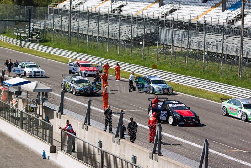 Auto's en technici op het net bij kring Monza stock foto