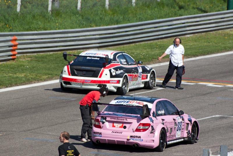 Auto's en technici op het net bij kring Monza stock afbeeldingen