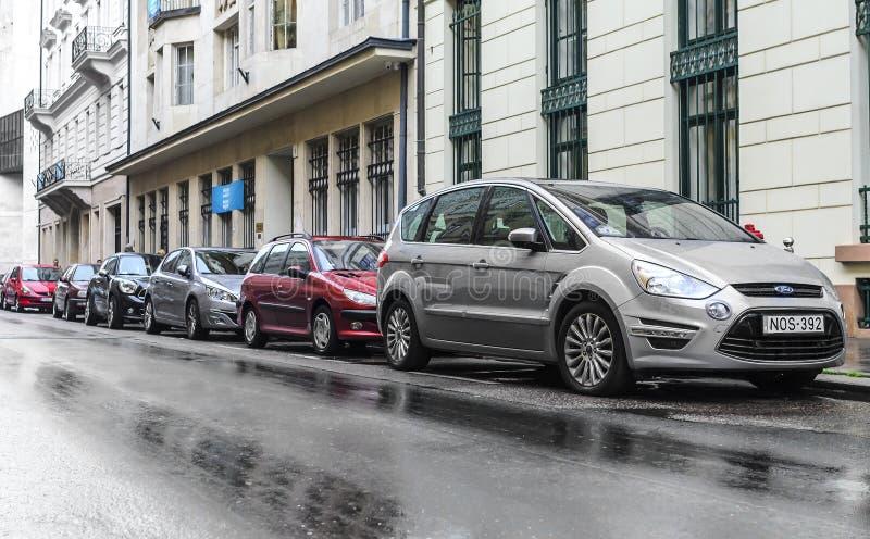 Auto's in het straatparkeren op een regenachtige dag stock foto