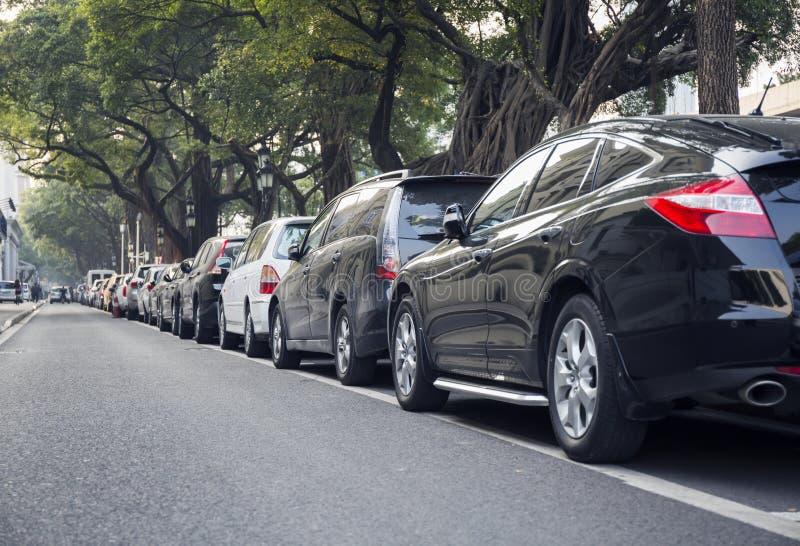 Auto's in lijn, rij van geparkeerde auto's op kant van de weg van stadsstraat stock afbeelding