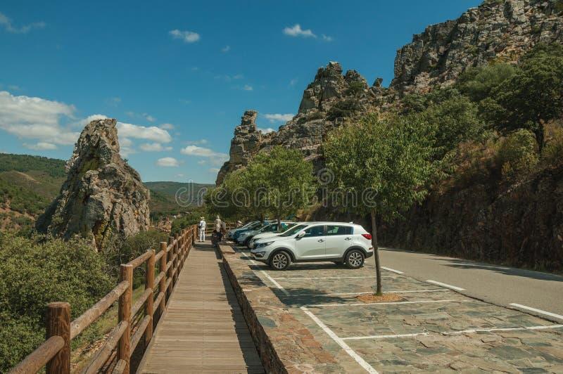 Auto's naast weg door rotsachtige klippen worden geparkeerd die stock fotografie