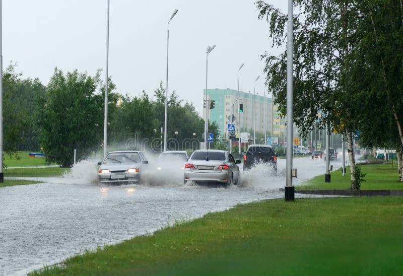 Auto's op een overstroomde straat in de stad royalty-vrije stock fotografie
