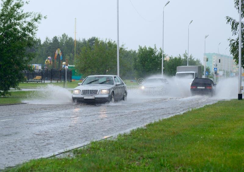 Auto's op een overstroomde straat in de stad stock foto